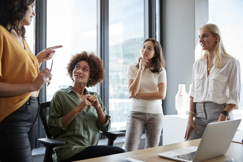 Four female colleagues in discussion at a desk in a creative office, three quarter length, close up royalty free stock images