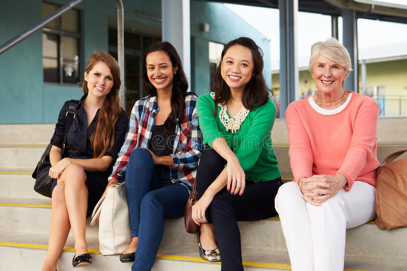 Four female teachers sitting on steps at entrance of school stock images