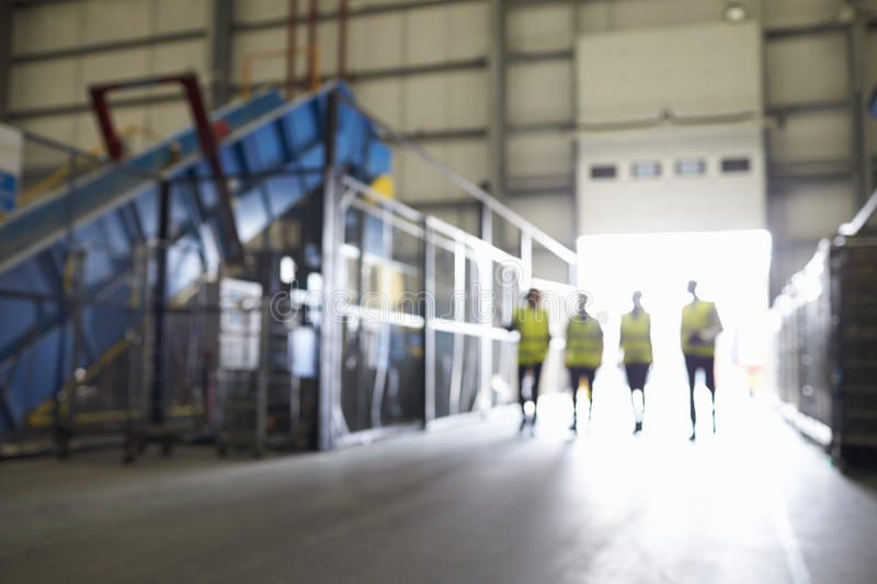 Four figures walking in an industrial interior, soft focus royalty free stock photography