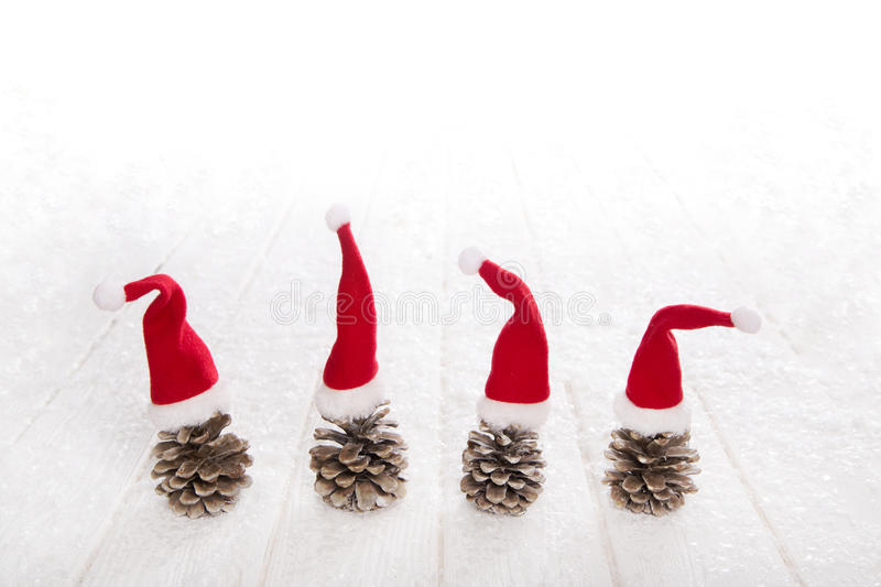 Four fir cone with red santa hats on snowy white wooden backgrou stock photos