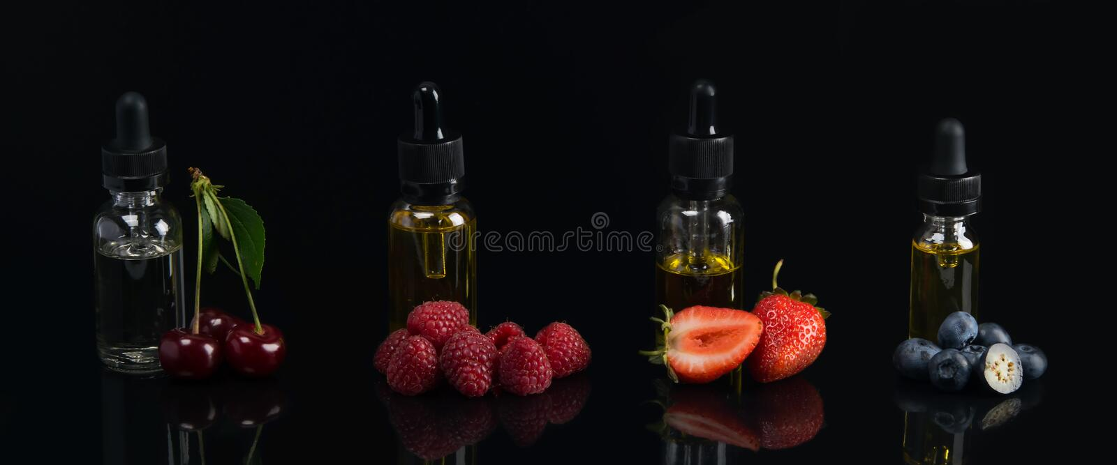 Four flavor flavors, in glass containers, on a black background, with a taste of cherries, strawberries, raspberries, blueberries, stock photos