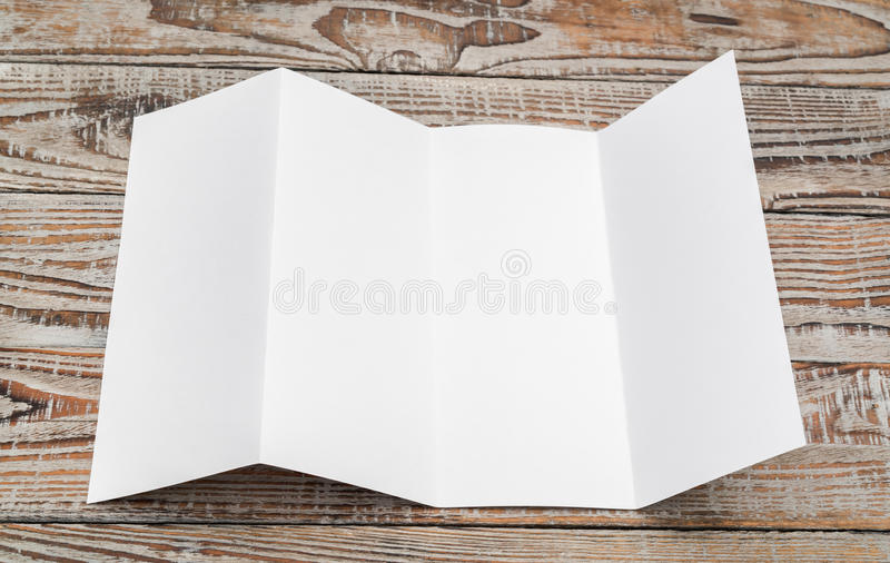 Four - fold white template paper on wood texture . Four - fold white template paper on wood texture royalty free stock photos
