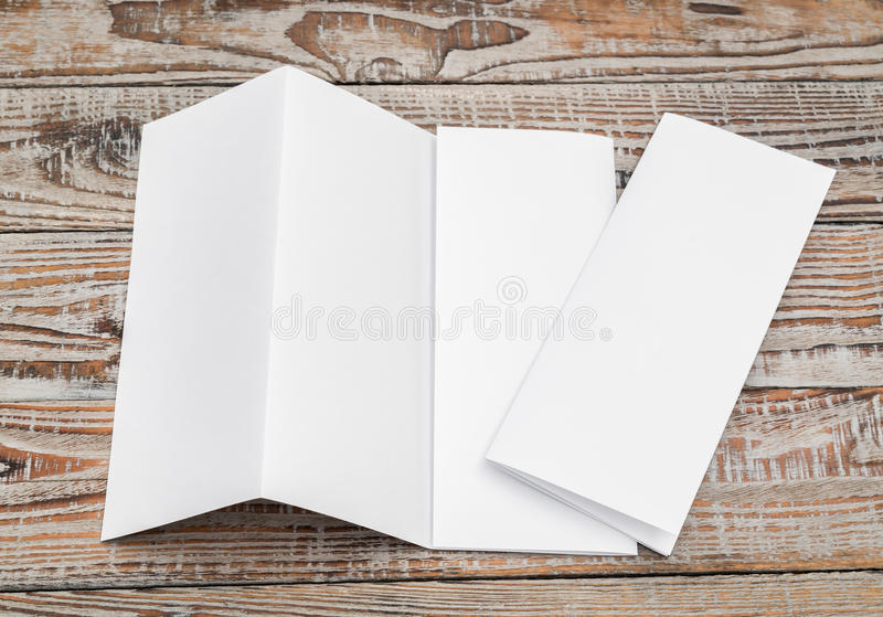 Four - fold white template paper on wood texture . Four - fold white template paper on wood texture stock photography