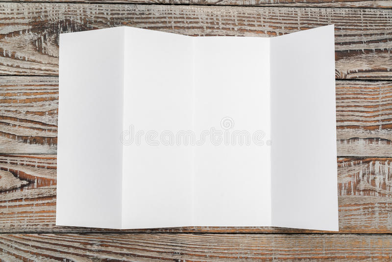 Four - fold white template paper on wood texture . Four - fold white template paper on wood texture stock photo