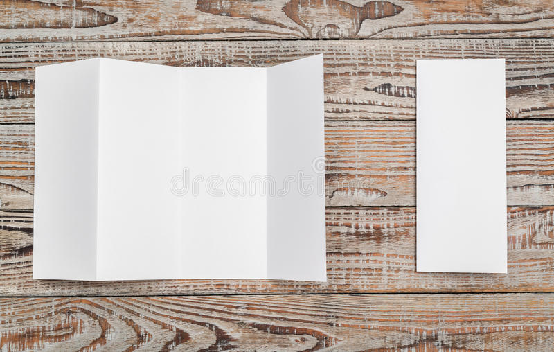 Four - fold white template paper on wood texture . Four - fold white template paper on wood texture stock photos
