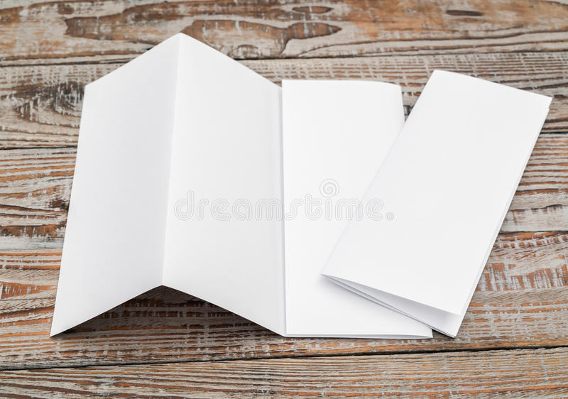 Four - fold white template paper on wood texture . Four - fold white template paper on wood texture royalty free stock image