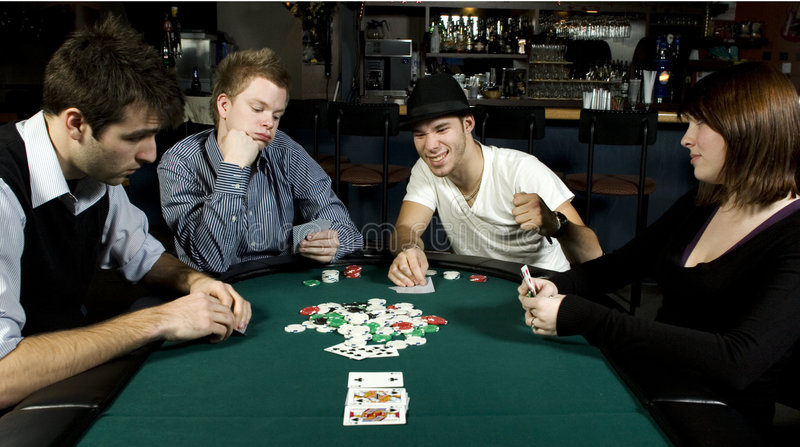 Four friends around table playing poker royalty free stock image