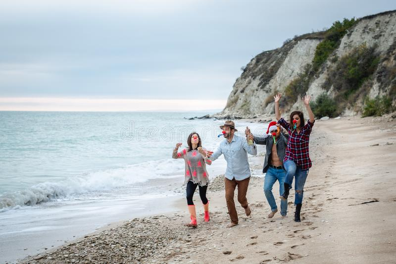 Four friends celebrate New Year`s Eve on the beach. Friends running together on a beach with red noses and colored whistles royalty free stock photography