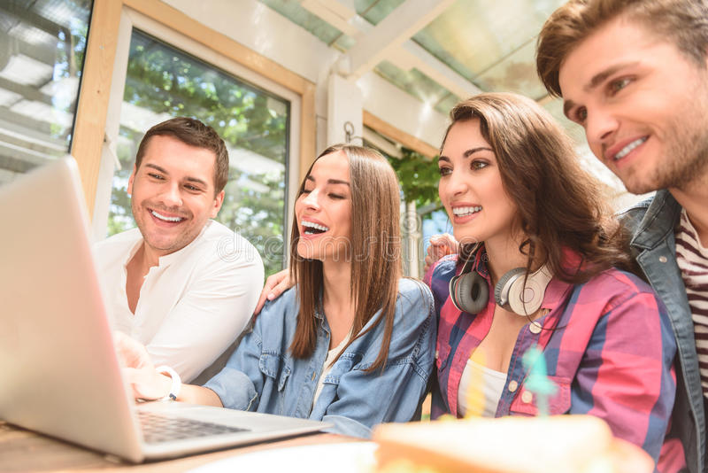 Four friends in coffee shop using laptop. Checking their social networking profiles. Close up of group smiling friends hanging out in coffee shop with laptop stock photography