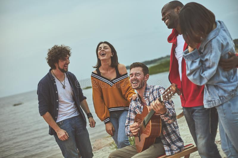 Group of happy friends are singing on seaside royalty free stock photo