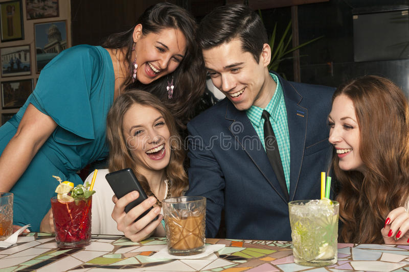 Four friends look at photograps of a man in his cell phone royalty free stock photography