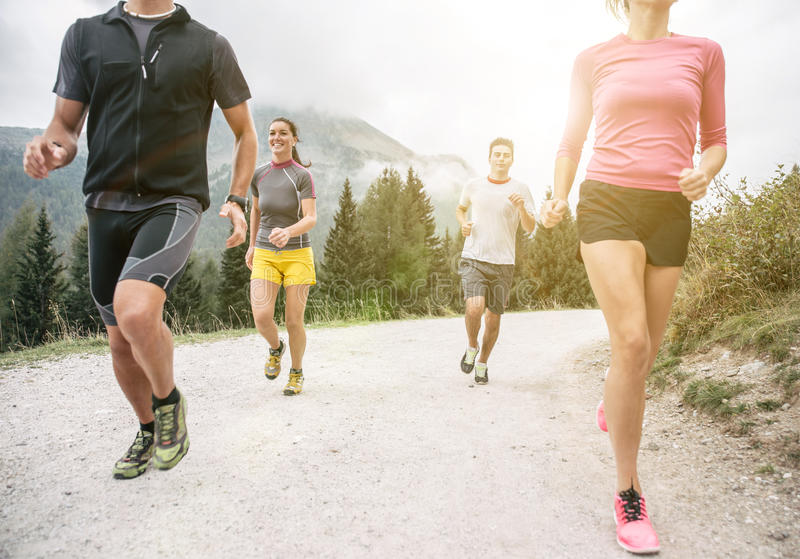 Four friends running off road on the mountains royalty free stock image