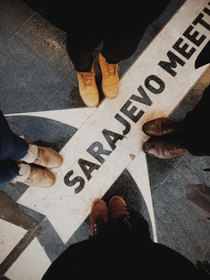 Four friends taking pictures of their feet in Sarajevo royalty free stock photo