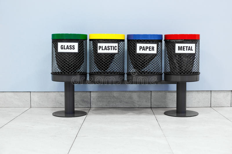 Four garbage bins. On wall background royalty free stock photo