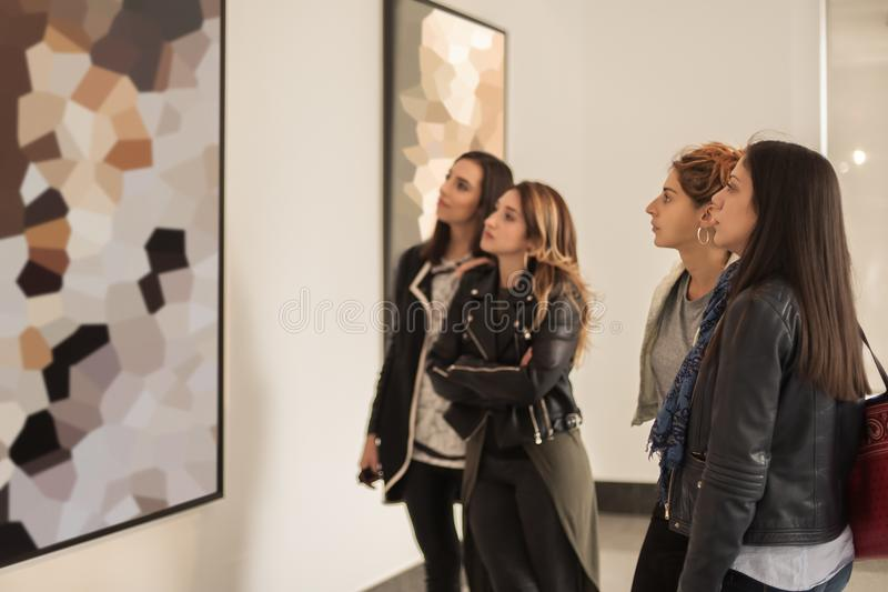 Four girl friends looking at modern painting in art gallery. Abstract painting stock photography