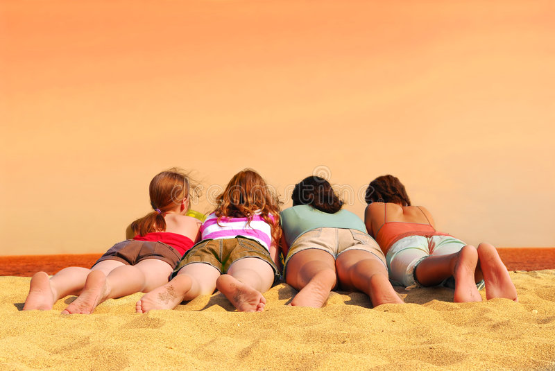 Four girls at orange sea. Four girls lying on a beach with orange sea and sky stock photography