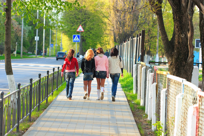 Four girls walking along the street royalty free stock photos