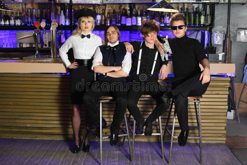 Four glamorous rock band pose near bar counte. Four glamorous rock band in black and white pose near bar counter royalty free stock image
