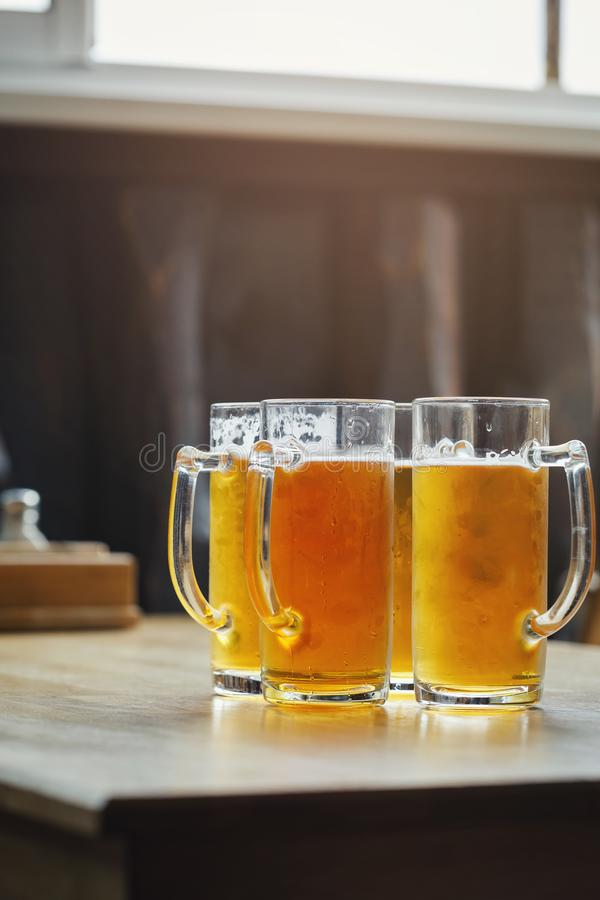 Four glasses of light beer in a bar on a wooden table royalty free stock photography