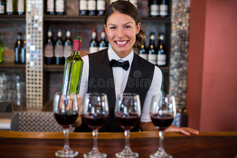Four glasses of red wine ready to serve on bar counter. While bartender holding a bottle in background stock image