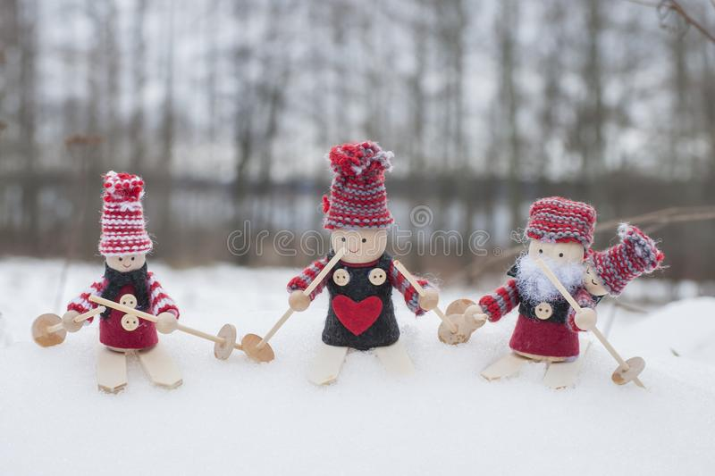 Four gnomes in knitted hats on skis in snowy landscape in Christmas time. Christmas background with four gnomes in knitted hats on skis in snowy landscape royalty free stock image