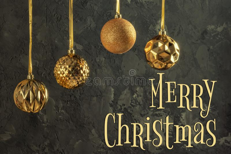 Four gold-colored Christmas balls are hanging by a ribbon. Beautiful composition with an inscription Merry Christmas on stock images
