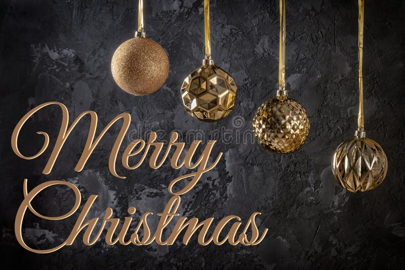 Four golden Christmas balls hanging on ribbons. Next to the inscription Merry Christmas on a black textured background. stock images