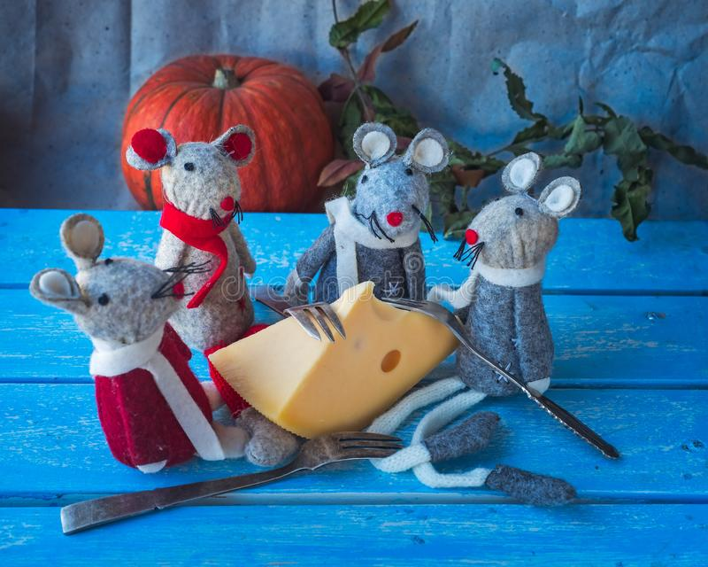 Four gray mouse gathered to eat cheese, Christmas card on a blue background, pumpkin in the background stock images