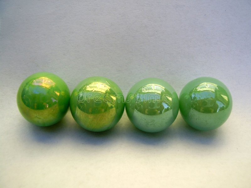 Four green marbles. Row of four green marbles, isolated on white background royalty free stock images