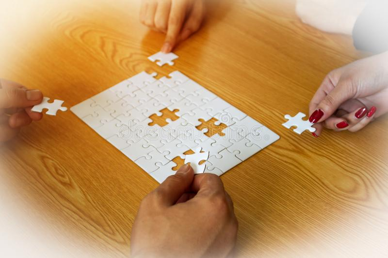 Four hands business worker help fill jigsaw puzzle to success stock photo