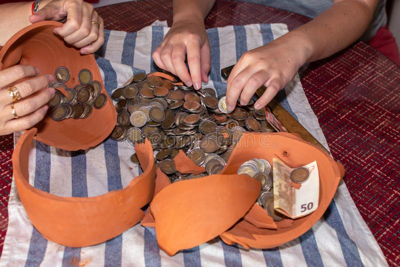 Four hands selecting coins from a piggy bank in the shape of a broken brown pig on a table royalty free stock photo