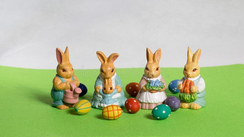 Four easter bunnies. child`s with eggs on green meadow royalty free stock image