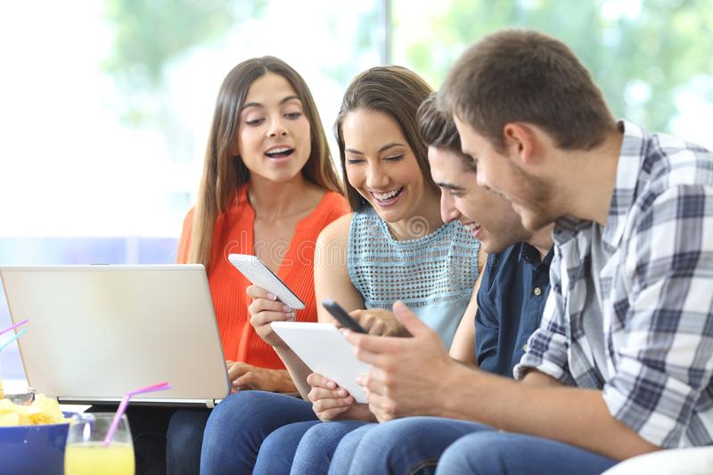 Four happy friends checking multiple devices at home royalty free stock images