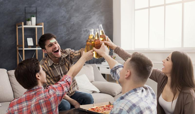 Four happy friends clinking beer bottles royalty free stock photo