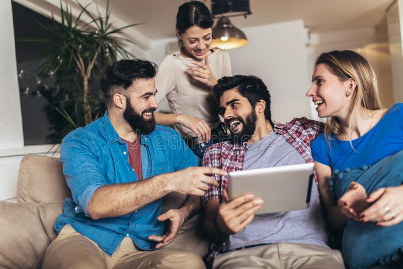 Happy friends laughing watching media content together in a tablet sitting on a sofa in the living room at home royalty free stock photo