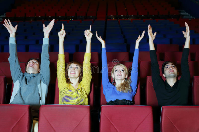 Four happy friends sit in cinema theater and pull hands up royalty free stock photography