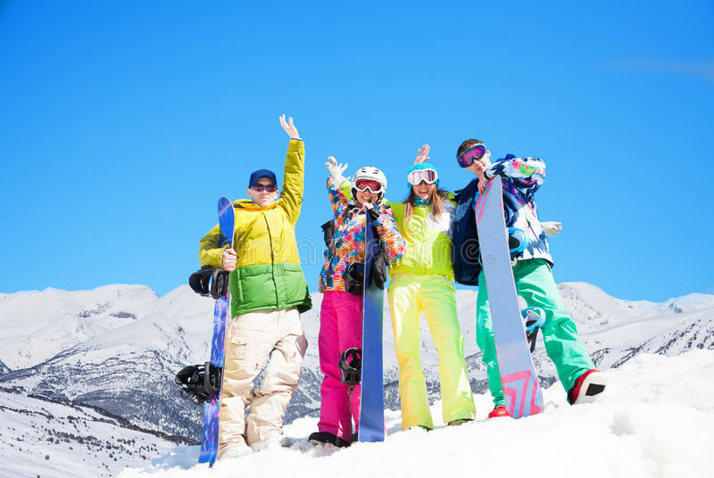 Four happy friends with snowboards