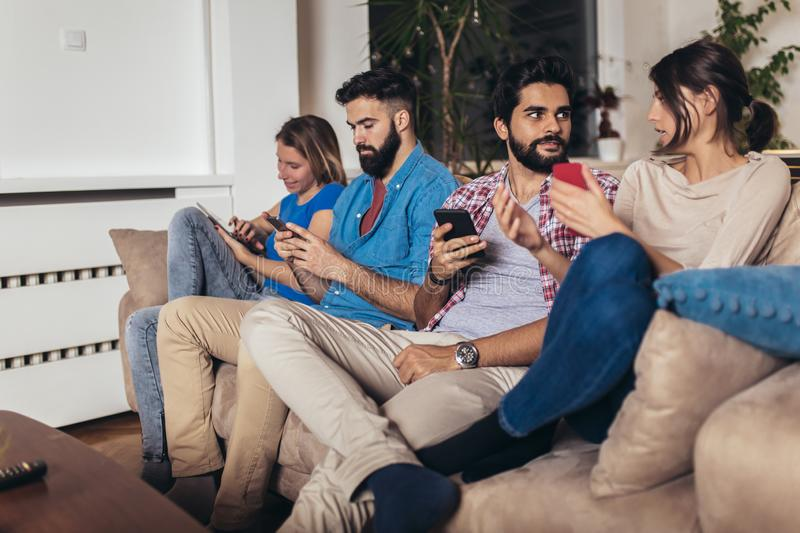Friends using their mobile phones sitting on a sofa at home stock photography