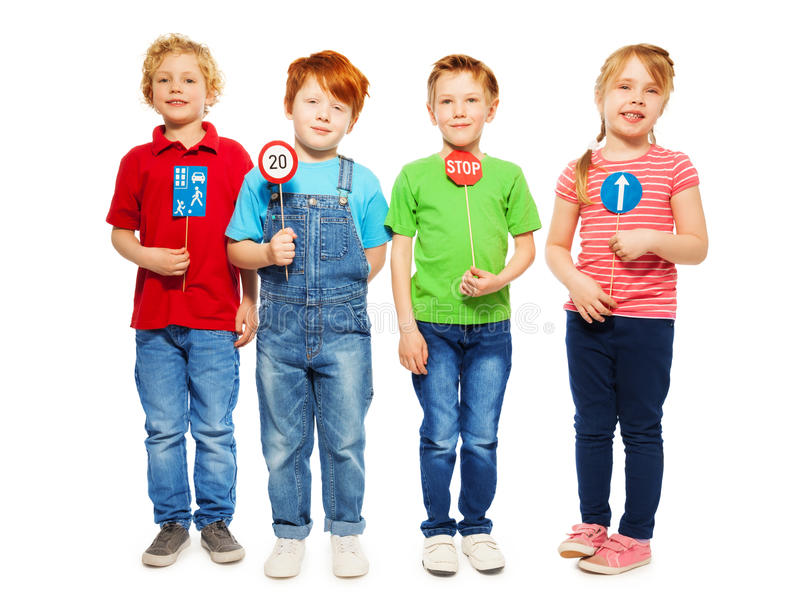 Four happy kids studying safety of traffic rules. Group of four kids, boys and girl standing in a row, holding small models of road signs, isolated on white stock image