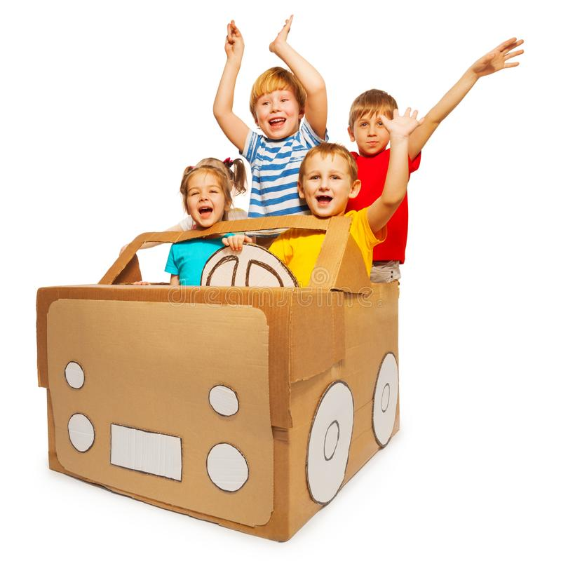 Happy kids waving hands sitting in cardboard car stock photos