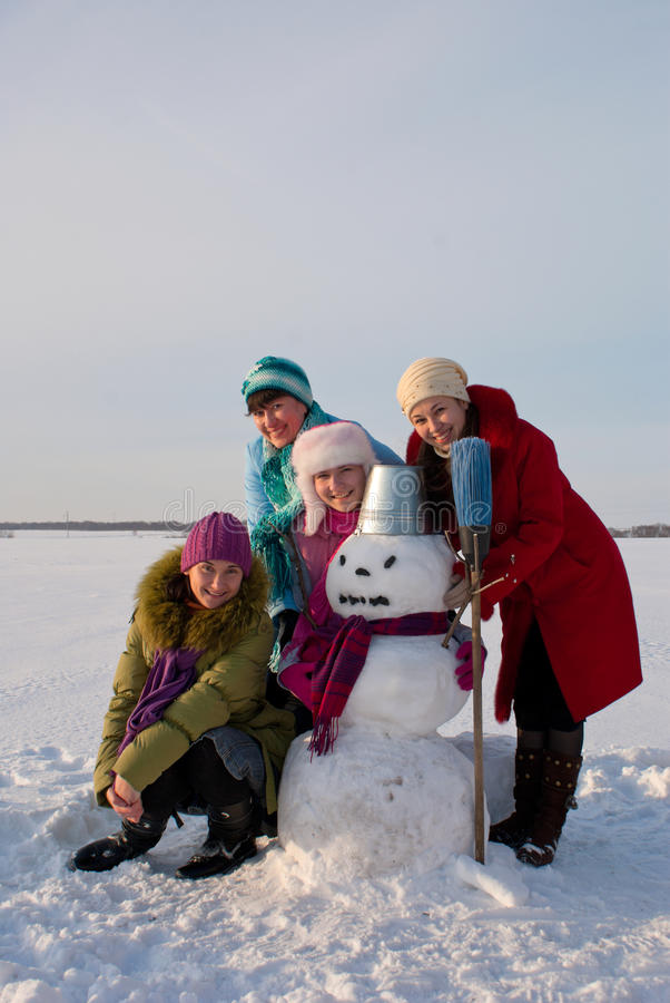 Four happy ladiesl with snowman royalty free stock image