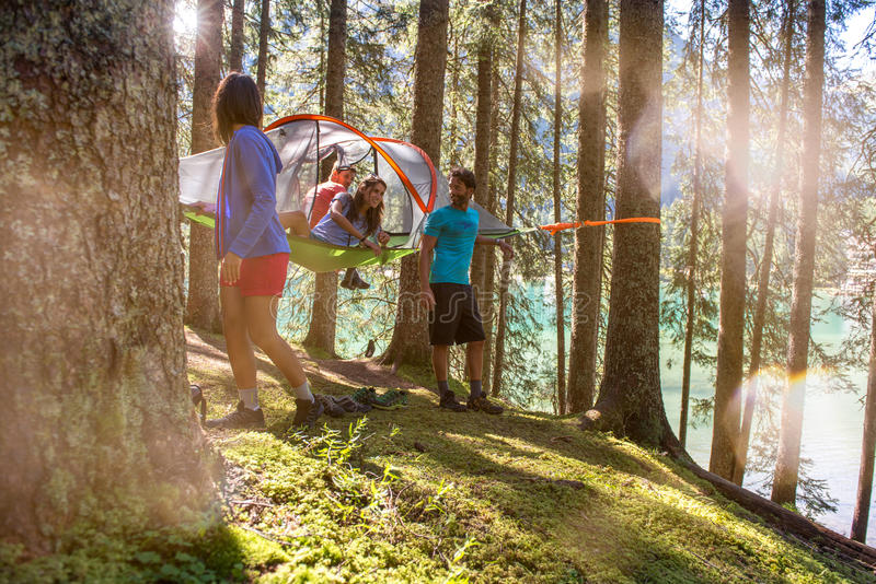Four happy man and woman hanging tent camping in forest woods during sunny day near lake.Group of friends people summer stock image