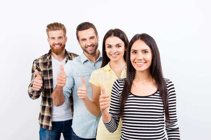 Four happy successful young prople are showing thumbs up on whi royalty free stock image