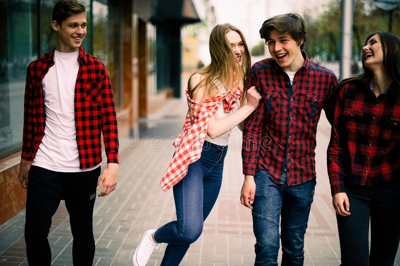Four happy trendy teenage friends walking in the city, talking each other and smiling. Lifestyle, friendship and urban life concep stock photography