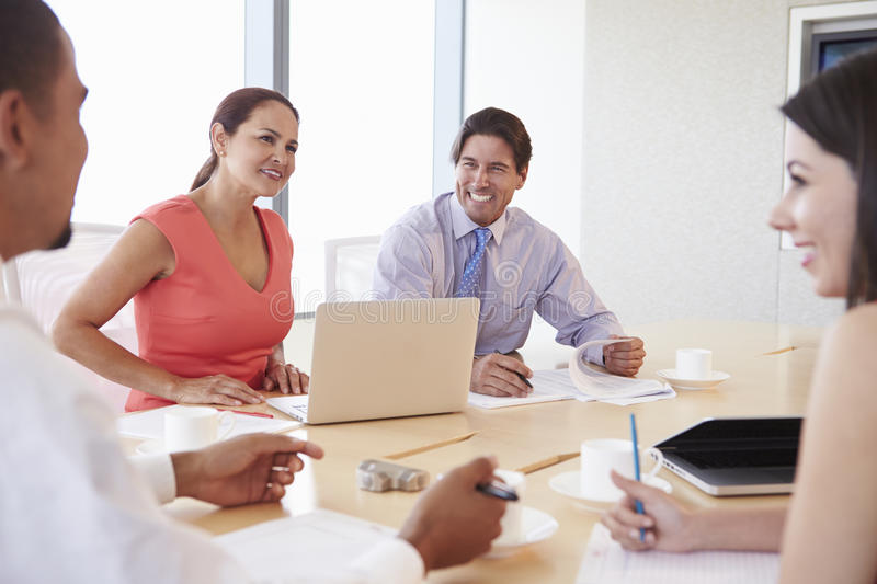 Four Hispanic Businesspeople Having Meeting In Boardroom royalty free stock image