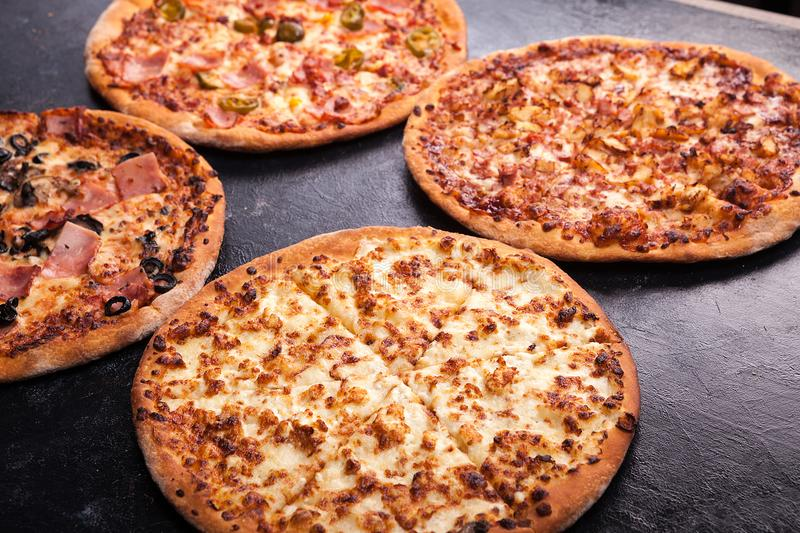 Four homemade different pizzas on dark wooden background stock image