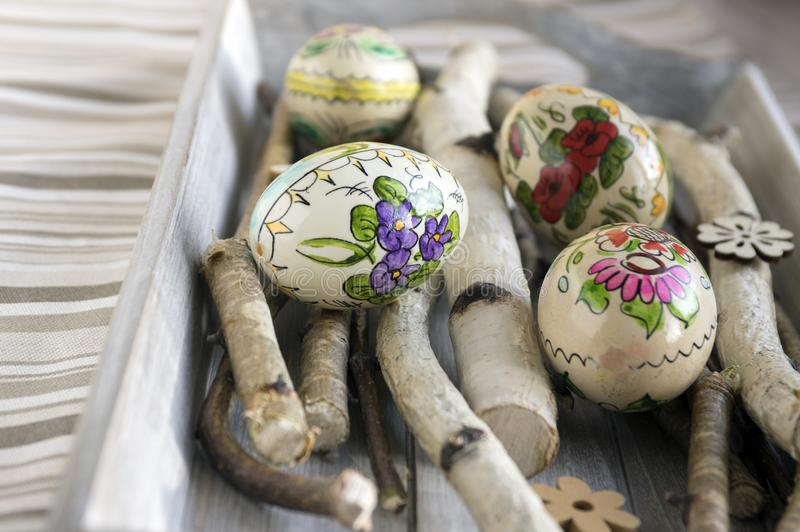 Four homemade and handmade Easter eggs with flower pictures on birch branches, czech ornaments, small wooden flowers royalty free stock images