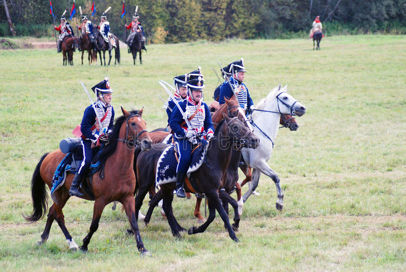 Four horses of different color and horse riders. MOSCOW REGION - SEPTEMBER 07, 2014: Four horses of different color - brown, black and white. Reenactors dressed royalty free stock image