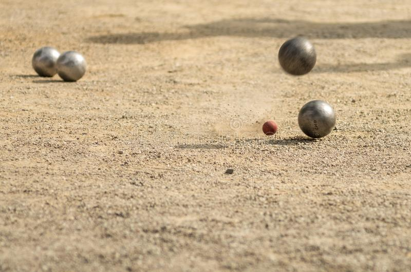 Petanque, game and sport with iron balls colliding with each other. Four iron balls, colliding with each other, on dirt floor, raising dust royalty free stock images