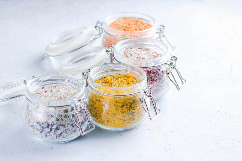 Four jars with different flavoured mixes of salt and spices. Himalayan and sea salt mixed with various peppers and herbs stock photography